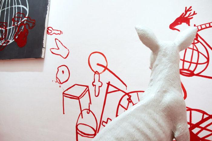 Amina Benbouchta, vue de son exposition au Cube - independent art room. Sculpture qui représente un kangourou blanc et dessins rouges au mur