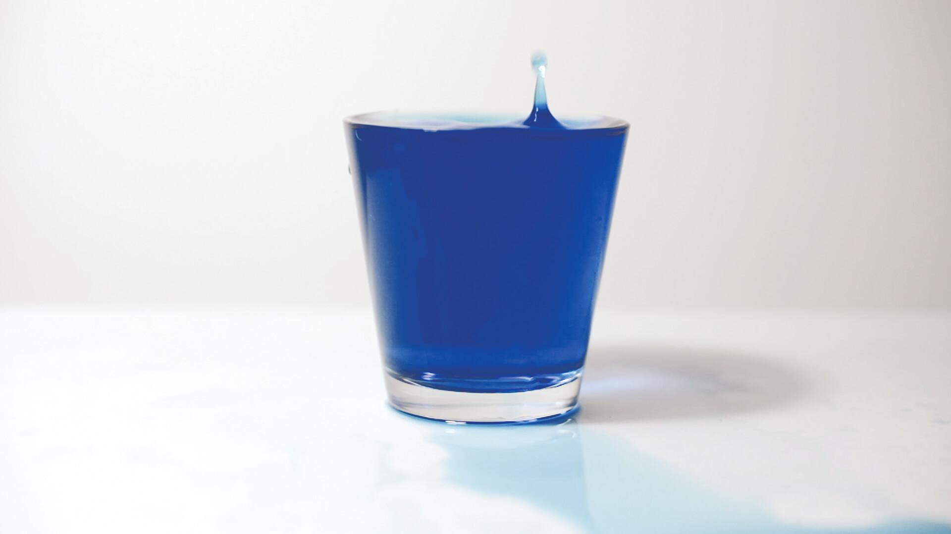 """Anna Raimondo, Mediterranio, vidéo dans laquelle une verre d'eau bleu se rempli goutte à goutte alors que l'artiste énumère en boucle le mot """"Méditerranée"""""""