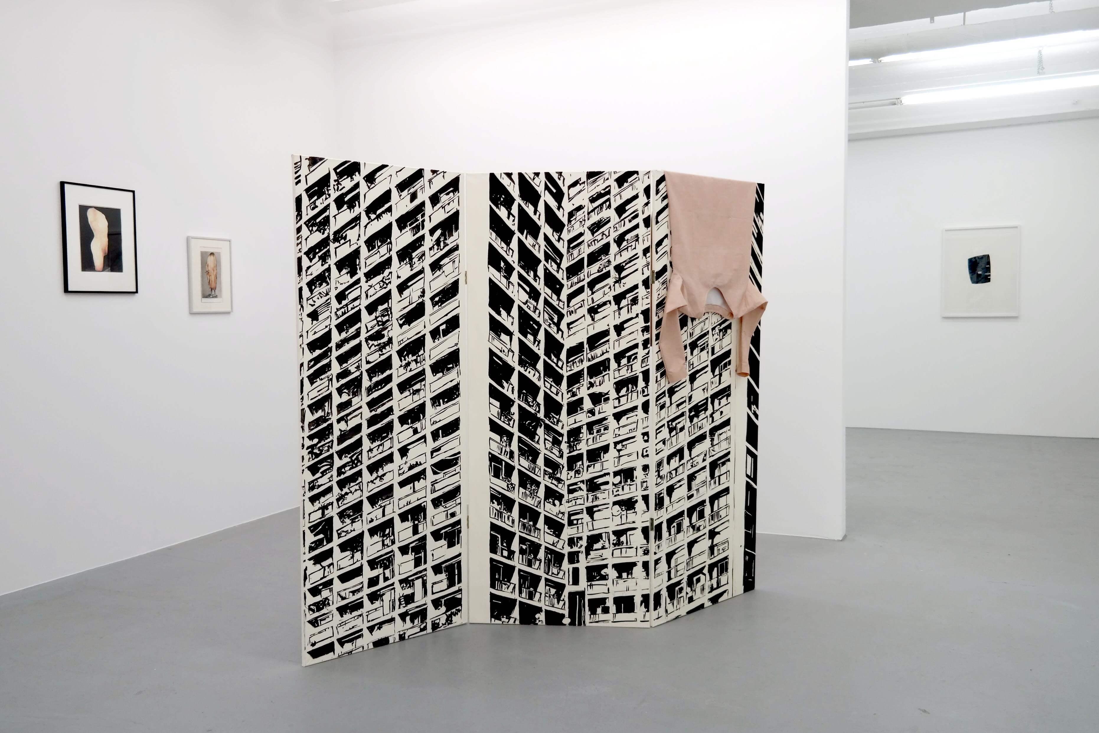 Katrin Ströbel, paravent sur lequel est dessinée la tour d'une immeuble , et polo couleur chaire