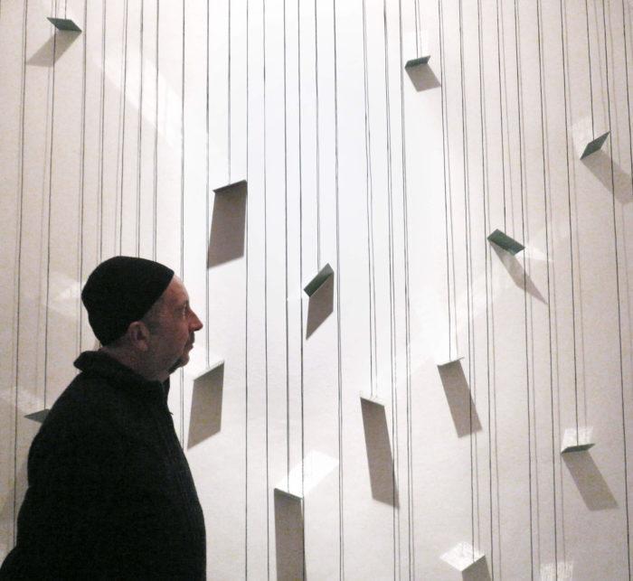 Josep Ginestar devant son installation constituée de miroirs et d'écritures qui se reflètent sur les murs du Cube - independent art room à Rabat, Maroc