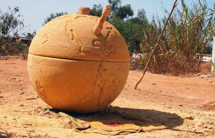 """Mohamed Arejdal, """"Crank"""" ou la manivelle du moulin. Grosse sculpture en sable du Maroc qui reprend le globe terrestre en le détournant en moulin pour faire de l'huile d'argan"""