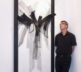 Hassan Echair devant un de ses tableau au Cube - independent art room, Rabat, Maroc