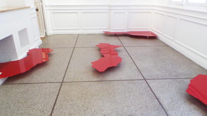 Zainab Andalibe Altérabilité géographique continents en verre rouge disposé dans l'espace d'exposition du Cube à Rabat, Maroc