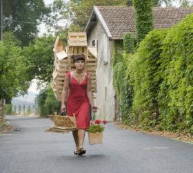 Gabriela Oberkofler, Buggelkraxen, photographie couleur de l'artiste transportant une maison en bois et cagettes sur le dos 2010